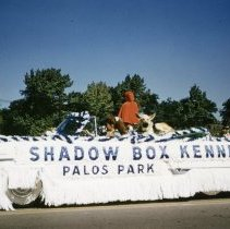 Image of Oak Lawn Round-Up Days Parade - This is a photograph of the Oak Lawn Round-Up Days Parade. It features a decorated convertible car representing Shadow Box Kennels located at 10360 S. Harlem in Palos Park moving westbound on 95th Street just past 50th Avenue. A dog rides on the top and there appears to be another figure possibly riding in the car and dressed in a red hooded cape. Spectators can be seen lining the parade route in the background.