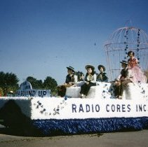Image of Oak Lawn Round-Up Days Parade - This is a photograph of the Oak Lawn Round-Up Days Parade. It features a float representing Radio Cores, Inc. located at 9540 S. Tulley in the Round-Up parade. The parade is moving westbound on 95th Street just past 50th Avenue. Spectators can be seen lining the parade route in the background.