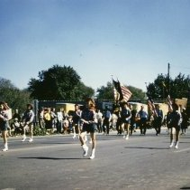 Image of Oak Lawn Round-Up Days Parade - This is a photograph of the Oak Lawn Round-Up Days Parade. It features the Marching Majorettes followed by members of the American Legion moving westbound on 95th Street just past 50th Avenue. Oak Lawn Motors and Brakes, located at 5000 W. 95th Street, is partially visible in the background and spectators can be seen lining the parade route.