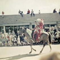 Image of Oak Lawn Round-Up Days Parade - This is a photograph of the Oak Lawn Round-Up Days Parade. It features a woman dressed as an Indian maiden riding a horse in the parade as it moves eastbound on 95th Street at 55th Avenue. Spectators can be seen lining the parade route along the street, on top of cars, and on the rooftops of the businesses, such as the Oak Lawn Construction Company located at 5501 W. 95th Street.