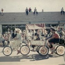 Image of Oak Lawn Round-Up Days Parade - This is a photograph of the Oak Lawn Round-Up Days Parade. This is a photograph of the Oak Lawn Round-Up Days Parade. It features decorated bicycles and a cart from Beverly Lawn in the parade as it moves eastbound along 95th Street at 55th Avenue. The riders sport 1940s handlebar moustaches, derby hats and the women matching dresses and headbands. Spectators can be seen lining the parade route along the street, on top of cars, and on the rooftops of the businesses, such as the Oak Lawn Construction Company located at 5501 W. 95th Street.