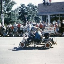 """Image of Oak Lawn Round-Up Days Parade - This is a photograph of the Oak Lawn Round-Up Days Parade. It features a go-kart, its driver and passenger wearing cowboy hats, carrying a sign that says """"Be kind to small cars"""" in the parade as it moves eastbound along 95th Street at 55th Avenue. Spectators can be seen lining the parade route along the street, on top of cars, and on the rooftops of the businesses, such as the Oak Lawn Construction Company located at 5501 W. 95th Street."""