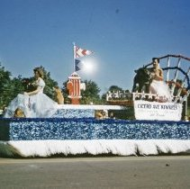 Image of Oak Lawn Round-Up Days Parade - This is a photograph of the Oak Lawn Round-Up Days Parade. It features a float representing the Cicero Avenue Kennels, located at 8700 S. Cicero Avenue, as it moves westbound on 95th Street just past 50th Avenue. Two women ride on the float with several dogs. A large fire hydrant topped with flags decorates the middle of the float. Spectators can be seen lining the street along the parade route in the background.
