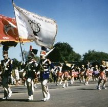 Image of Oak Lawn Round-Up Days Parade - This is a photograph of the Oak Lawn Round-Up Days Parade. It features the Horace Mann Band complete with flag carriers and baton twirlers from Gary, Indiana moving westbound on 95th Street just past 50th Avenue. Oak Lawn Motors and Brakes, located at 5000 W. 95th Street, is partially visible in the background and spectators can be seen lining the parade route.