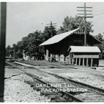 Image of Wabash Railroad Depot - This is a photograph of the Wabash Railroad Depot located on the north side of the tracks at Cook Avenue and Wabash Avenue (now known as Yourell Drive). A cart is visible on the train platform. Signal lights are visible at different cross streets down the tracks. In the foreground, there appears to be a chain ladder hanging down from one of the railroad signal poles.