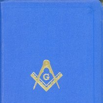 Image of Masonic Bible - This item is a Mason Bible used by the Oak Lawn Masonic Lodge 1166 located at 9420 South 52nd Avenue. It was presented to Brother Harry Moise in 1960 and used for a period thereafter. The Bible contains a number of names of local residents including Wiley Simmons. The cover is blue in color with gold symbols and lettering.