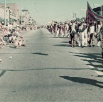 Image of 1976 Oak Lawn Bicentennial Parade - This is a photograph 1976 Oak Lawn Bicentennial Parade. Crowds are seen lining the sidewalks as a colonial costumed band marches by. The parade is traveling westbound on 95th Street just past Fernwood Smith Cleaners located at 5114 W. 95th Street. The Brandt building, located at 5131 W. 95th Street is partially visible on the right.