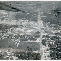 Image of Aerial Photo of 95th Street and Southwest Highway - This is an aerial photograph of the intersection of 95th Street and Southwest Highway. 95th Street can be seen running from the top (east) to the bottom (west) in the picture. Oak Lawn Community High School can be seen in the left center of the picture. Various other businesses in the area are also visible such as Fisher's Motel near the school, the Suburban Transit bus depot just east of the intersection, the Fairway grocery store on the left (south) side of 95th Street. The Oak Lawn water tower located at 9437 S. Cook is visible in the distance. The underside of the airplane wing and a wing strut are visible in the very top of the picture.