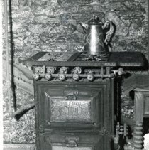 "Image of 'Reliable' Gas Stove - This is a photograph of the ""Reliable"" Gas Stove that was patented a few years before gas service came to Evergreen Park and Oak Lawn in 1909. The stove came in one color, black, and a supply of matches was needed for cooking. The manufacturer of the stove was Schneider & Trenkamp Company out of Cleveland, Ohio. This photo relates to the Oak Lawn Golden Jubilee 50th Anniversary and appeared in the 1959 Special Edition of the Southwest Suburbanite."