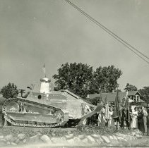 Image of War Memorial Ceremony - This is a photograph of a ceremony taking place at the war memorial located at 95th Street and Columbus Avenue. The Army WWI armoured tank arrived at the flagpole site in November of 1940. It was painted overall aluminum or silver. The tank was later given as scrap to aid the war effort during WWII. It was later replaced with an M-5 Stuart Tank which still stands at the location.