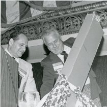 Image of Illinois Municipal League Annual Conference, 1975-1976 - This is a photograph of Fred M. Dumke (left) at the annual conference of the Illinois Municipal League held at the Conrad Hilton Hotel in Chicago. He appears to be presenting a gift to another unidentified member of the league.