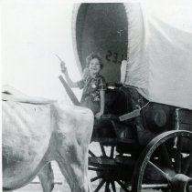 Image of Janice McCarty - This is a photograph of Janice McCarty on a covered wagon at the Oak Lawn Round-Up Days celebration. She is holding a toy pistol. The animal pulling the wagon is partially visible and appears to be an ox.
