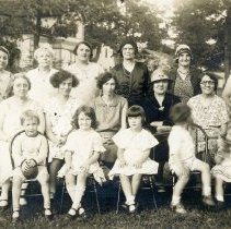 Image of 1920s Get-Together - This is a photograph of a late 1920s get-together at an unidentified location. Left to right, rear: unidentified, unidentified, Minnie Hageman, Lettie Harnew, Elsie Elvidge, Thora Bronson. 2nd row: Laura Phillips, unidentified, unidentified, unidentified, unidentified, unidentified, Mrs. Preseton. Front row: unidentified. Several homes can be seen in the background.