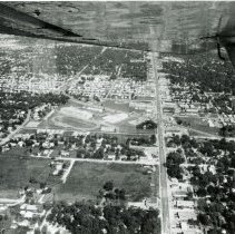 Image of Aerial Photograph of 95th Street and Southwest Highway - This is an aerial photograph of the intersection of 95th Street and Southwest Highway. 95th Street can be seen running from the top (east) to the bottom (west) in the picture. Oak Lawn Community High School can be seen in the left center of the picture. Various other businesses in the area are also visible such as Fisher's Motel near the school, the Suburban Transit bus depot just east of the intersection, the Fairway grocery store on the left (south) side of 95th Street. The Oak Lawn water tower located at 9437 S. Cook is visible in the distance. The underside of the airplane wing and a wing strut are visible in the very top of the picture.