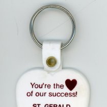 Image of St. Gerald's Promotional Key Chain - This item is a promotional key chain for St. Gerald school. It is white in color with red lettering and features an image of a heart.