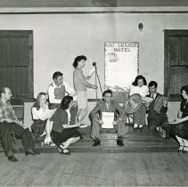"Image of ""Rio Grande Hotel"" Cast - This is a photograph of the cast of ""Rio Grande Hotel"" rehearsing for the show in a room in Covington School on November 6th or 7th, 1945. The cast from left to right are unidentified, Theodore A. Thomas, Sr., Ella Smith, Henry Hiorns, Agnes Hiorns, Vivien Schneider, Captain William J. Morris, Shirley Gillice, Manuel Mann, and Mrs. Carl Lambrighnt (Eva Stewart)."
