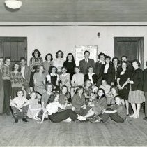 "Image of ""Rio Grande Hotel"" Cast - This is a photograph of the cast of ""Rio Grande Hotel"" posing in a room in Covington School on November 6th or 7th, 1945. In the back row ninth from the left is Arthur Adams and thirteenth from the left is Frank Wilson (tap dancer). Doris Hoffman is in the front. The rest of the cast is unidentified."