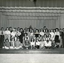 "Image of ""Rio Grande Hotel"" Cast - This is a photograph of the cast of ""Rio Grande Hotel"" posing in the Covington School auditorium on November 6th or 7th, 1945. The production was sponsored by The Mothers of WWII-Unit One. In the front row 7th from the left is Gwendolyn Lane.  In the second row 1st on the left is Winifred Reynolds. In the third row 2nd from the left is Frank Wilson (tap dancer); 4th through 6th are Mrs. Maude Frederick, Mrs. Carl Lambright, and Shirley Gillice; 9th and 10th are Vivien Schneider and Mrs. Manuel Mann (Ida). In the back row 2nd and 3rd from the left are Clifford Reynolds and Henry Hiorns; 7th through 10th are Ella Smith, Morrie Twigg, Theodore A. Thomas, Sr., and Agnes Hiorns; 12th is Manuel Mann."
