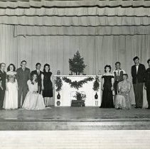 "Image of ""Rio Grande Hotel"" Cast - This is a photograph of the cast of ""Rio Grande Hotel"" posing in the Covington School auditorium on November 6th or 7th, 1945.  From left to right are Mrs. Carl Lambright (Eva Stewart), Theodore A. Thomas, Sr., Shirley Gillice, Arthur Adams, Ella Smith, Manuel Mann, Agnes Hiorns, Vivian Schneider, Henry Hiorns, unidentified, Morrie Twigg, and Clifford Reynolds."
