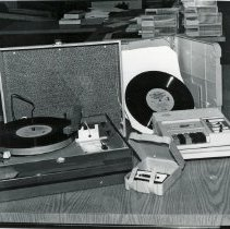 Image of Fine Arts Department Specialized Equipment - This is a photograph of some of the specialized equipment, known as 'talking books', available in the Fine Arts Department of the Oak Lawn Public Library. The items include a phonograph and audio books for the blind recorded on 8 1/3 rpm records, cassette tapes, and a cassette tape player.