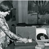 Image of Fine Arts Department Specialized Equipment - This is a photograph of library staff member Madeline Reed demonstrating some of the specialized equipment, known as 'talking books', available in the Fine Arts Department of the Oak Lawn Public Library. The items include a phonograph and audio books for the blind recorded on 8 1/3 rpm records, cassette tapes, and a cassette tape player. In the background, snow covered mobile homes in the Pine Tree Trailer Court located at 9400 S. Raymond Avenue are visible. The Village-owned trailer court was demolished in 1989 to make room for the Oak Lawn Public Safety Center.