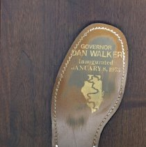 Image of Governor Dan Walker Award Plaque - This item is an award plaque given to Dr. Thomas V. Powell by Illinois Governor Dan Walker. The mounted shoe references an event where he crossed the state in 1971 by walking nearly 1,200 miles. Walker served as Governor from 1973-1977 and in 1987 was charged with bank fraud. As for Powell, he was mayor for a short time in 1973 after defeating Fred M. Dumke. The results were later reversed by a court decision and recount.
