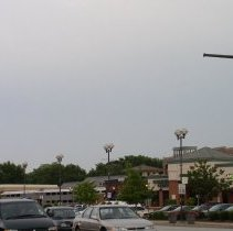 Image of 95th Street and 52nd Avenue - This is a photograph of the shopping center located at 95th Street and 52nd Avenue in Oak Lawn. This view shows cars moving westbound on 95th Street. In the shopping center, the Potbelly sandwich shop located at 5129 W. 95th Street, Starbucks Coffee, located at 5135 W. 95th Street, and a Game Crazy store located at 5137 W. 95th Street are visible. In the background, a commuter train is stopped at the Oak Lawn Metra station.