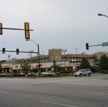 Image of 95th Street and 52nd Avenue - This is a photograph of the shopping center located at 95th Street and 52nd Avenue in Oak Lawn taken from the north side of 95th Street just east of 52nd Avenue and looking southeast. The roof of the Oak Lawn Metra Station and the Oak Lawn-Patriot Metra parking garage are partially visible to the left and above the stores. In the shopping center, the Potbelly sandwich shop located at 5129 W. 95th Street, Starbucks Coffee, located at 5135 W. 95th Street, and a Game Crazy store located at 5137 W. 95th Street, Hollywood Video located at 5141 W. 95th Street and a Cingular Wireless store located at 5145 W. 96th Street are visible. The Harris Bank building is partially visible on the left as is the former Mal's Mens Shop located at 5201 W. 95th Street. The overhead stoplights and a road sign marking 95th Street as US Rt12-20 East are also visible.