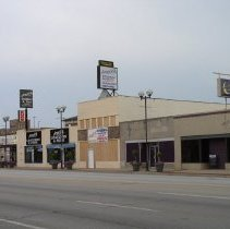 Image of 5100 Block of 95th Street - This is a photograph of the businesses in the 5100 block on the south side 95th Street in Oak Lawn taken from the north side of 95th Street and looking southeast. The Oak Lawn-Patriot Metra parking garage and the Harris Bank building located at 5151 West 95th Street are partially visible above the stores. Businesses seen in this picture include the former Mal's Mens Shop located at 5201 W. 95th Street, Annie's Ltd. at 5203 W. 95th Street, Congressman Dan Lipinski's's office at 5205 W. 95th Street, Expressline Fitness for Women at and the Goal Post Lounge at 5207 W. 95th Street, Angelo's Leathers & Furs at 5209 W. 95th Street which is in the process of expanding in this photograph. Also visible is the Deja Brew Bar & Grille located at 5219 W. 95th Street.