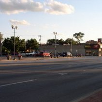 Image of 95th Street and 53rd Avenue - This is a photograph of the intersection of 95th Street and 53rd Avenue taken from the north side of 95th Street and looking southwest. On the left or east, the 5200 block has been demolished in anticipation of redevelopment. To the right, or west, businesses along the 5300 block included Joon Lee's Tae Kwon Do Academy, St. James Place, and Dolores Interiors.