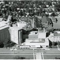 Image of Aerial Photograph of Little Company of Mary Hospital  - This is an aerial photograph (looking west) of the Little Company of Mary Hospital located at 95th Street between California and Fransisco Avenues in Evergreen Park. California Avenue runs left to right in the bottom of the photo. Most of the hospital structures have since been demolished and replaced with new buildings. St. Bernadette Catholic Church, located at 9343 S. Francisco Avenue can be seen in the middle right of the photo. A residential neighborhood of homes can be seen stretching to the west of the hospital.