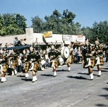Image of Oak Lawn Round-Up Days Parade, 1952 - This is a photograph of the 1952 Oak Lawn Round-Up Days Parade. It features a group of bagpipers wearing kilts. The name on the drum identifies the group as the Chicago Stockyards American Legion. The parade is moving westbound on 95th Street at about 54th Avenue. The Oak Lawn Linoleum & Tile Company located at 5408 W. 95th Street, Service Cleaner's located at 5404 W. 95th Street, and Lee's Food Shop located at 5402 W. 95th Street are seen in the background. Spectators can be seen lining the parade route, some sitting on the top of what appears to be a vehicle.