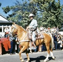 Image of 1952 Oak Lawn Round-Up Days Parade - This is a photograph of the 1952 Oak Lawn Round-Up parade. It features a man on horseback believed to be Bob Atcher, singing cowboy of radio and television, in the Round-Up parade as it is moving westbound on 95th Street just past 54th Avenue.