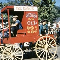 Image of 1952 Oak Lawn Round-Up Days Parade - This is a photograph of the 1952 Oak Lawn Round-Up parade. It features the Doc Ratajik Wizard Oil wagon moving westbound on 95th Street just past 54th Avenue. The Ratajik Pharmacy was located at 5269 W. 95th Street. Spectators can be seen lining the sidewalk to watch the parade.