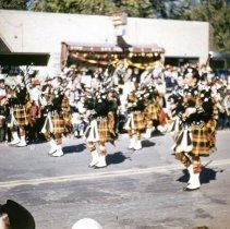 Image of 1952 Oak Lawn Round-Up Days Parade - This is a photograph of the 1952 Oak Lawn Round-Up Days Parade. It features the Chicago Stockyards American Legion bagpipers. The parade is moving westbound on 95th Street at about 54th Avenue. Service Cleaner's located at 5404 W. 95th Street, and Lee's Food Shop located at 5402 W. 95th Street are seen in the background. Spectators can be seen lining the parade route.