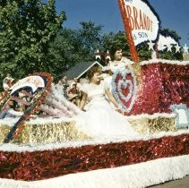 Image of 1952 Oak Lawn Round-Up Days Parade - This is a photograph of the 1952 Oak Lawn Round-Up Parade. It features a float representing Brandt and Son, Inc, a building materials company located at 9520 51st Avenue, in the Round-Up parade as it moves westbound on 95th Street just past 54th Avenue. Two unidentified women are riding on the float. The Oak Lawn Linoleum & Tile Company located at 5408 W. 95th Street can be seen in the background. Spectators can be seen lining the parade route.