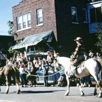 Image of 1952 Oak Lawn Round-Up Days Parade - This is a photograph of the 1952 Oak Lawn Round-Up Parade. It features Horse Thief Harry being paraded through town on a horse with a noose around his head while his captor rides behind him on another horse. They are passing the M&F Restaurant located at 5420 W. 95th Street. It has been renamed as the Grub Palace for Round-Up. Spectators can be seen lining the parade route, many sitting on automobiles of the era.
