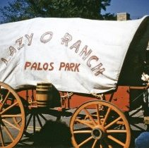 Image of 1952 Oak Lawn Round-Up Days Parade - This is a photograph of the 1952 Oak Lawn Round-Up Parade. It features a covered wagon from the Lazy O Ranch located in Palos Park moving eastbound on 95th Street at 54th Avenue. The Oak Lawn Linoleum & Tile Company located at 5408 W. 95th Street can be seen in the background and spectators can be seen lining the parade route. Riders from the Lazy O Ranch put on horse show during Round-Up Days which featured trick riding and roping.