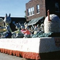 Image of 1952 Oak Lawn Round-Up Days Parade - This is a photograph of the 1952 Oak Lawn Round-Up Parade. It features a float from Dean's Dairy. The float features a bevy of little bunnies holding out glasses to a mommy bunny holding a Dean's Milk carton. The float is moving westbound down 95th Street at about 54th Avenue. They are passing the M&F Restuarant located at 5420 W. 95th Street and Sodaro's Grocery and Ice Cream store located at 5424 W. 95th Street can be seen in the background. Spectators can be seen lining the parade route.