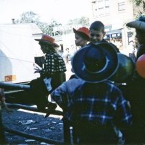 Image of 1952 Oak Lawn Round-Up Days Parade - This is a photograph of a group of children sitting on a fence along the route of the 1952 Oak Lawn Round-Up parade. Some type of vehicle can be seen in the left background, its orange license plate visible. Some of the children are wearing cowboy hats and wearing toy gun in holsters around their waists. One boy is dressed as an Indian. A boy on the right is holding two balloons. In the background the Sinclair Gasoline sign at Safeway Motor Sales and Service located at 5252 W. 95th Street is visible as is Nick's Tap Room located at 5220 W. 95th Street to the right. A police officer is also visible in the background between the children on the right.
