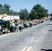 Image of 1952 Oak Lawn Round-Up Days Parade - This is a photograph of the 1952 Oak Lawn Round-Up parade as it moves down 95th Street toward 54th Avenue. Spectators can be seen lining the parade route on both sides of 95th Street. Some are sitting on the hoods and roofs of automobiles and trucks of the era and many are dressed in Western wear. Several police officers are seen stationed along the route for crowd control. Oak Lawn Linoleum & Tile Company located at 5408 W. 95th Street, Service Cleaner's located at 5404 W. 95th Street, and Lee's Food Shop located at 5402 W. 95th Street can be seen to the left behind the spectators. A photographer can be seen crouched in the middle of the street as vehicles in the parade approaches.
