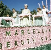 Image of 1952 Oak Lawn Round-Up Days Parade - This is a photograph of the 1952 Oak Lawn Round-Up Parade. It features a float sponsored by Marcellin's Beauty Salon which was located at 5001 W. 95th Street. Four women ride the float past the 5400 block of 95th Street. In the background, Oak Lawn Linoleum and Tile store located at 5408 W. 95th Street.