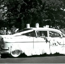 Image of Welcome Wagon Courtesy of Jack Thompson Oldsmobile - This is a photograph featuring an unidentified woman driving the Oak Lawn Welcome Wagon in  the 1954 Oak Lawn Round-Up Days Parade. Cars for the Welcome Wagon program were provided courtesy of Jack Thompson Oldsmobile, which was located at 4040 W. 95th Street. The car is decorated with fringe, a gift basket on the hood and gift bags on the roof. Spectators and chairs can be seen lining the parade route.
