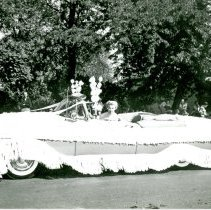 Image of Jack Thompson Oldsmobile Float, 1954 - This is a photograph featuring an unidentified woman driving a 1954 Oldsmobile 98 from Jack Thompson Oldsmobile in the 1954 Oak Lawn Round-Up Days Parade. Jack Thompson Oldsmobile was located at 4040 W. 95th Street. The car is decorated with bows and fringe along the top and bottom. Jack Thompson Oldsmobile is spelled out across the length of the car. In the background, spectators can be seen lining the parade route.