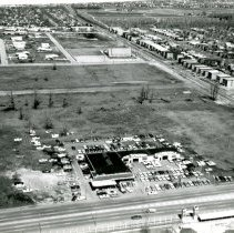 Image of Aerial Photo of Jack Thompson Oldsmobile - This is an aerial photograph featuring Jack Thompson Oldsmobile dealership located at 4040 W. 95th Street. The picture is taken looking north. In the upper middle of the picture, Trinity Evangelical Covenant Church located at 9230 S. Pulaski (Crawford) is visible. Some scattered residential homes can be seen to the west (left) of the church. The more densely populated area in the far background is Hometown. St. Mary's Catholic Cemetery, Evergreen Park, is visible in the upper right of the picture. Housing to the east (right) of the church is in Evergreen Park. The entrance of the Green Oak Kiddyland amusement park can be seen in the immediate foreground at the bottom of the picture. The amusement park was formerly located on the south side of 95th Street at Pulaski (Crawford) and operated from 1946 to 1971.