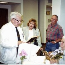 Image of Vic Dunneback - This is a photograph featuring Vic Dunneback, a library security guard opening a gift, possibly on the occasion of his retirement, in one of the lower level meeting rooms of the library. Louise Pfieffer, a library staff member, Don Suchy, head of Maintenance, and Bernice Dunneback, Vic's wife look on.