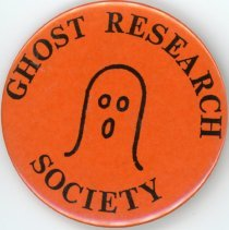 Image of Ghost Research Society Promotional Button - This item is a button promoting the Ghost Research Society of Oak Lawn. It is orange in color and features an image of a ghost in the center. The organization was founded in 1977 and is still active today.