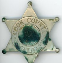 Image of Cook County Police Department Badge - This item is a Cook County Police Department badge believed to have been used by a member of the Eichler Family. It is silver in color and features an emblem in the center.