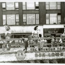 Image of Round-Up Days Promotional Float - This is a photograph of a promotional Round-Up float sponsored by Lions Club International. It features a number of girls in Western themed dress and appears to have been taken in Chicago.