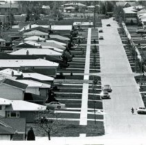 Image of 9900 Block of Kilbourn Avenue - This is an aerial photograph of the 9900 block of Kilbourn Avenue in Oak Lawn looking from the north to the south. This area was a new development during a housing boom in the suburbs in the early 1970s. Streets, sidewalks, and driveways line the block of new homes. Cars are seen parked in driveways while children can be seen on bicycles and playing baseball near a park in the background. In the left background, the Elim Evangelical Free Church located at 10000 S. Kostner is seen.